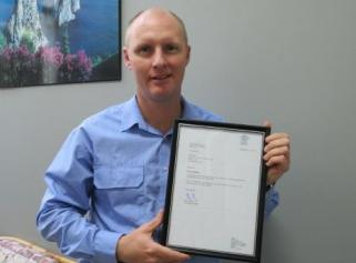 Paul with accreditation certificate
