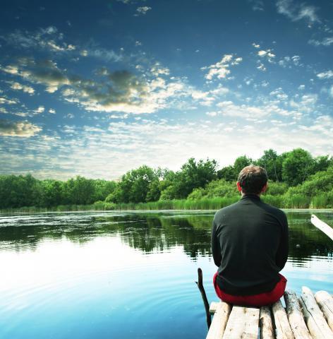 Man pondering on lake